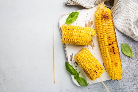 Grilled corn cobs with salt and spices on white background, top view Stockfoto