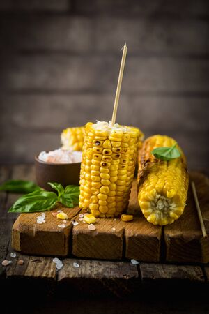 Grilled corn cobs with salt and spices on vintage wood background