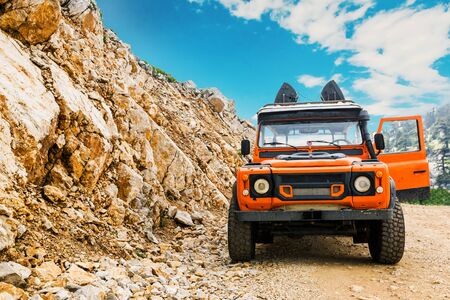 Four wheel drive vehicle 4x4 with all terrain tires parked in mountains