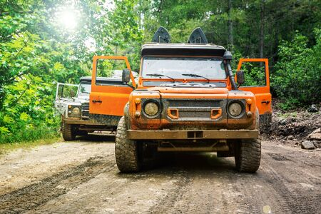 Dirty Four wheel drive truck 4x4 with all terrain tires parked in the forest