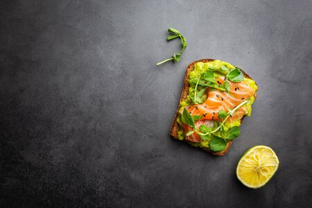 Toast with avocado cream and smoked salmon over black background, top view