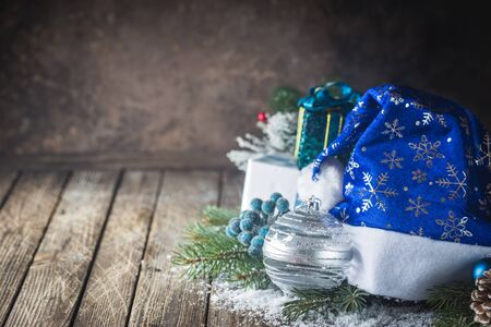 Christmas background with christmas balls, gift, Santa hat and snow on a wooden background Stock Photo