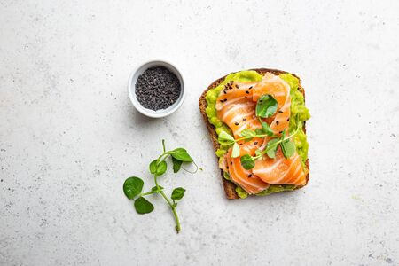 Toast with avocado cream and smoked salmon over white background, top view