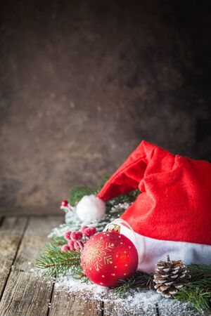 Christmas background with christmas balls, gift, Santa hat and snow on a wooden background 写真素材