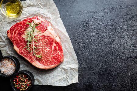 Raw fresh meat Ribeye Steak and seasonings on dark background, top view with copy space