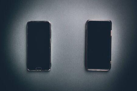 Two Smart Phones over black background, top view