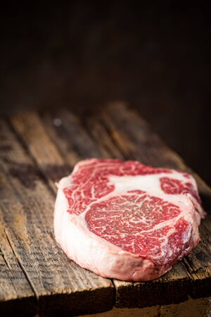Raw fresh meat Ribeye Steak and seasonings on wooden background, rustic style