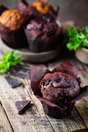 Dark chocolate muffin with mint on a wooden table, homemade baking