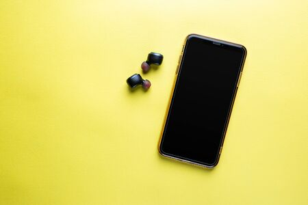 Mobile phone with wireless headphones isolated on yellow background - close-up view