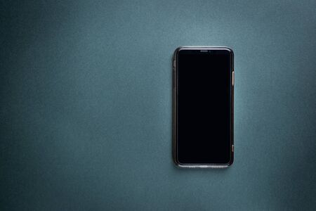 Modern Smart Phone over black background, top view