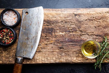 Cutting board, seasonings and oil set with meat cleaver on dark background, top view, copy space 免版税图像