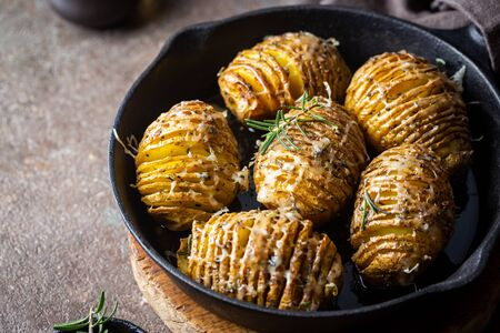 Baked hasselback potatoes with cheese, garlic and greens