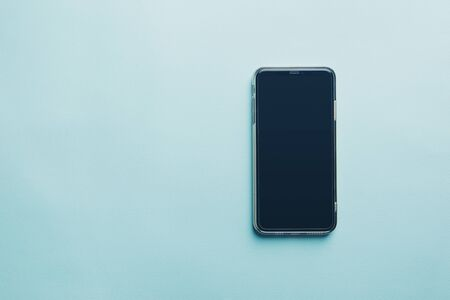 Modern Smart Phone over blue background, top view