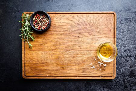 Cutting board, seasonings and oil set on dark background, top view, copy space Stock Photo