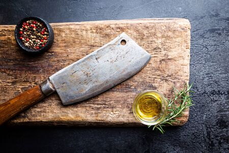 Cutting board, seasonings and oil set with meat cleaver on dark background, top view, copy space Stock fotó