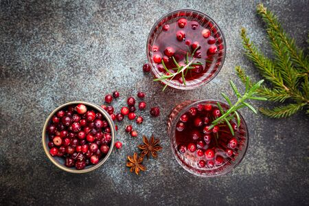 Fresh cranberry cocktail with rosemary in a glass on gray background, top view
