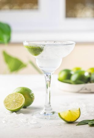 Refreshing Homemade Classic Alcoholic Margarita Cocktail with Lime and Salt on light background