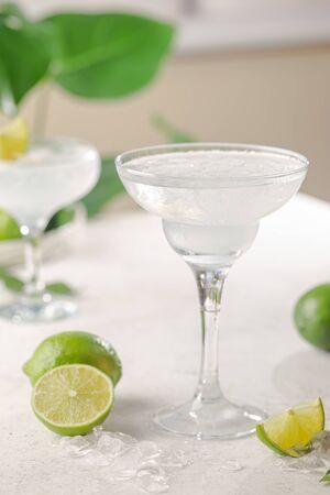 Cocktail de margarita alcoolique classique fait maison rafraîchissant avec citron vert et sel sur fond clair