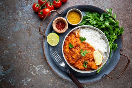Chicken meat with tikka masala sauce, spicy curry food in a bowl with rice and seasonings, top view Stock Photo