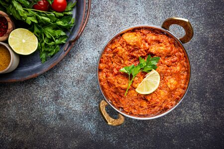 Chicken meat with tikka masala sauce, spicy curry food in iron copper pot with seasonings, top view