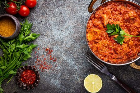 Chicken meat with tikka masala sauce, spicy curry food in iron copper pot with seasonings, top view Reklamní fotografie