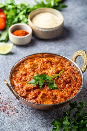 Chicken meat with tikka masala sauce, spicy curry food in iron copper pot with seasonings