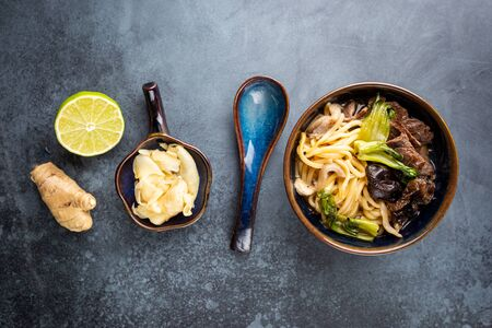 Asian ramen noodles soup with beef, oyster mushrooms and vegetables in bowl on gray background, top view Stock fotó