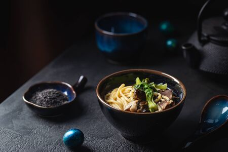 Soupe asiatique de nouilles ramen au bœuf, pleurotes et légumes dans un bol sur fond sombre