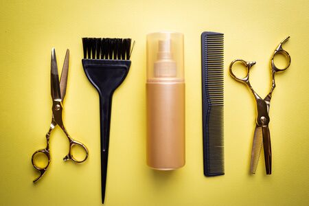 Various hair dresser and cut tools on yellow background with copy space 스톡 콘텐츠