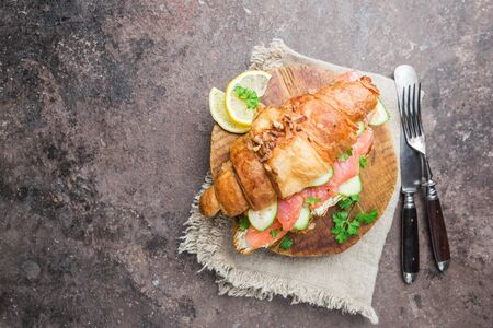 smoked salmon sandwich with cream cheese fresh and cucumbers on cutting board, top view Stockfoto