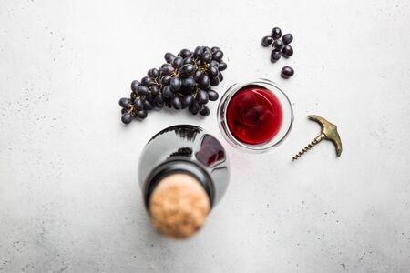 Red wine in a glass and ripe grapes on white background, top view Stok Fotoğraf