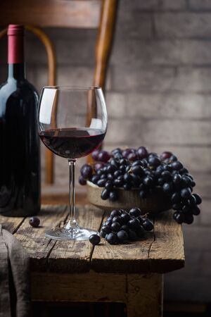 Red wine in a glass and ripe grapes on wooden table Stok Fotoğraf