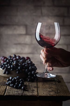Red wine glass in a men hand and ripe grapes on wooden background