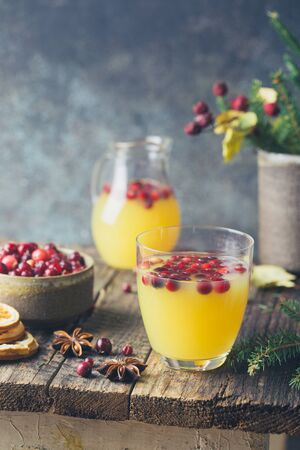 Spice fruity orange punch with cranberry in glass on wooden table Foto de archivo - 133572781
