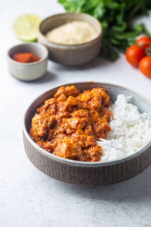 Chicken meat with tikka masala sauce, spicy curry food in a bowl with rice and seasonings