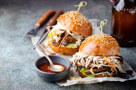 Pulled beef burger with cabbage salad and bbq sauce on paper Stock Photo
