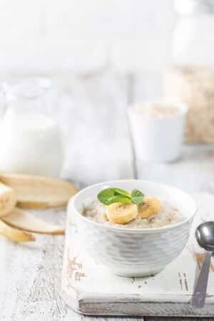 Bowl of oatmeal porridge with banana on white wooden rustic table, healthy breakfast, diet food.