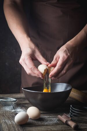 Professional chef hands are breaking an egg into bowl to make dough on wooden table, over dark background Standard-Bild - 134806741