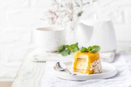 Piece of mango mousse cake on plate over white wooden table. Stock fotó