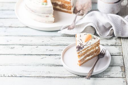 Healthy homemade carrot cake with cream cheese frosting on white wooden table