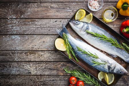 Fresh raw seabass and ingredients for cooking. Two fish seabass with lemon, spices and herbs on wooden table, top view with copy space. Zdjęcie Seryjne