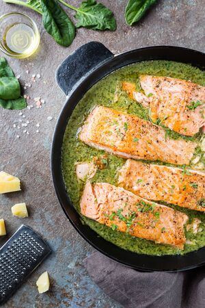 Grilled Salmon with spinach and garlic cream sauce in a frying pan, top view