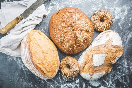 Assortment of fresh baked bread and buns on black background, top view Foto de archivo - 134807130