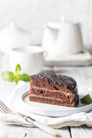 Delicious chocolate Prague cake on plate over white background