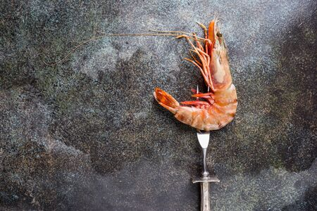 Giant Raw fresh Tiger Prawn over dark stone background, top view