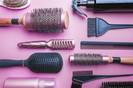 Various hair dresser and cut tools on pink background with copy space