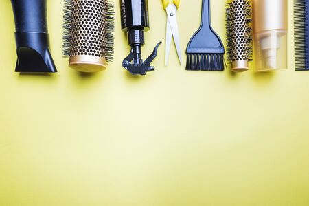 Various hair dresser and cut tools on yellow background with copy space Фото со стока