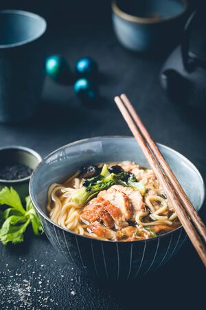 japanese soup with fried eel Yanagawa Nabe in a bowl on dark background