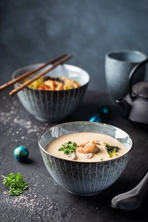 Tom Yum Kung soup, a Thai traditional spicy prawn soup in a bowl on dark background