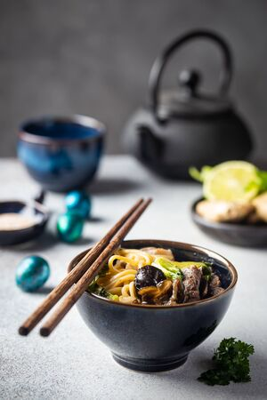 Asian ramen noodles soup with beef, oyster mushrooms and vegetables in bowl on gray background
